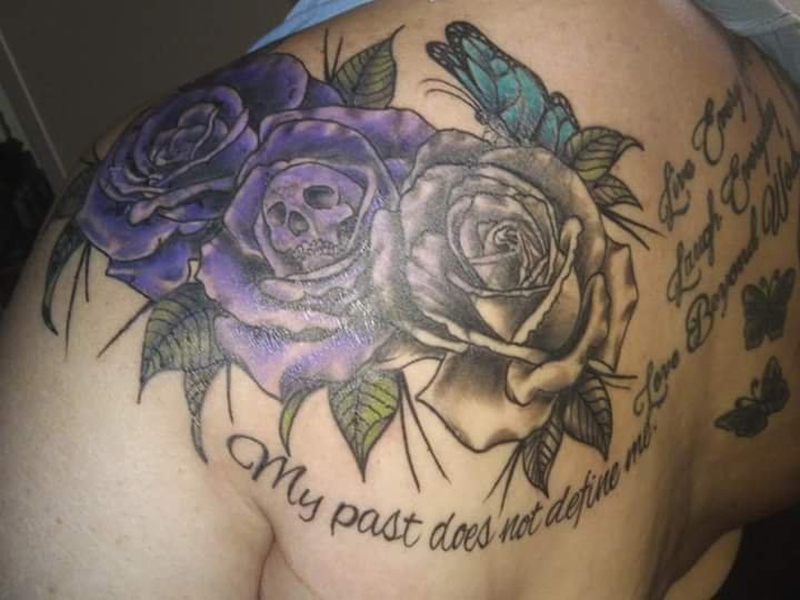 "tattoo of 3 purples roses with a skull in the center statig ""My past does not define my future"" subject:  Kimberlee Plezia Tattoo artist:  Makai Synner"