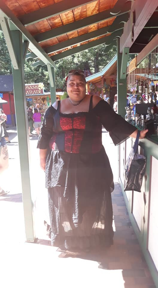 Kimberlee Plezia attending the Renaissance Festival in Larkspur, CO. Kimberlee is wearing a black linen with a black and red corset.